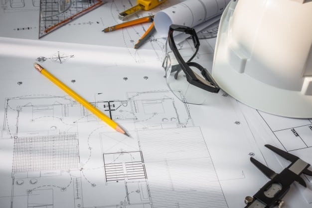 construction-plans-with-white-helmet-and-drawing-tools-on-bluepr_1232-2917